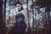 nízký úhel pohledu na elegantní ženu v čarodějnické maškarní stojící na pozadí lesa, pohled pryč