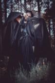 brunetka, Žena v čarodějnické maškarní a korunka na hlavě, držící ruce s černou textilkou v blízkosti obličeje, s pohledem