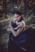 mladá žena v černém čarodějnice kostým stojící na lesním pozadí, dívá se na kameru