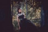 selektivní zaměření krásné ženy na kostým černé čarodějnice stojící mezi stromy