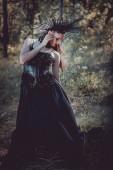dospělá žena v kostýmu černé čarodějnice, která stála na pozadí lesa a dívala se jinam