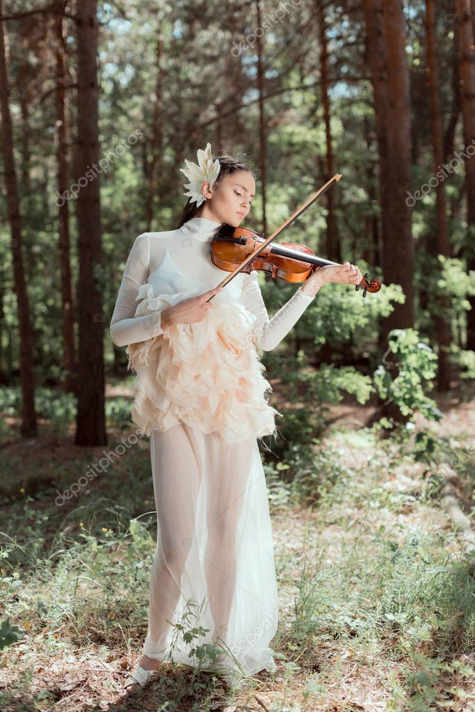 elegant woman in white swan costume standing on forest background, playing on violin