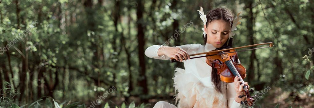 panoramic view of brunette woman in white swan costume playing on violin