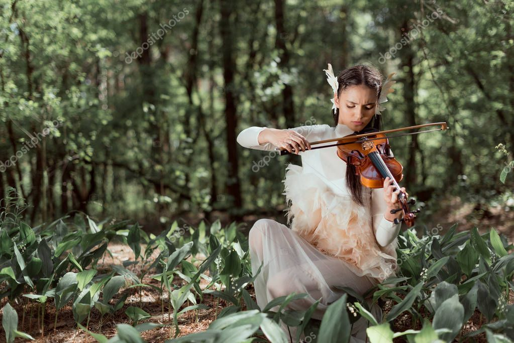 beautiful woman in white swan costume playing on violin