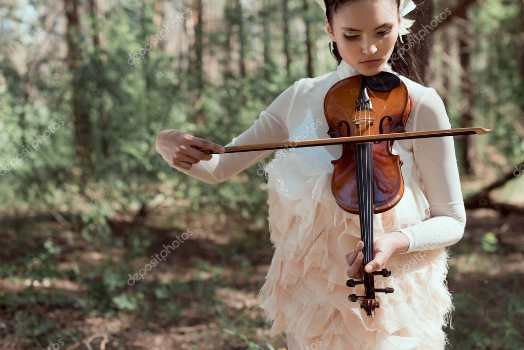 young woman in white swan costume standing on forest background with violin