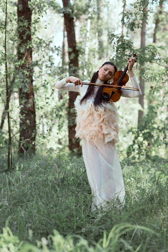 tender woman in white swan costume standing on forest background with violin
