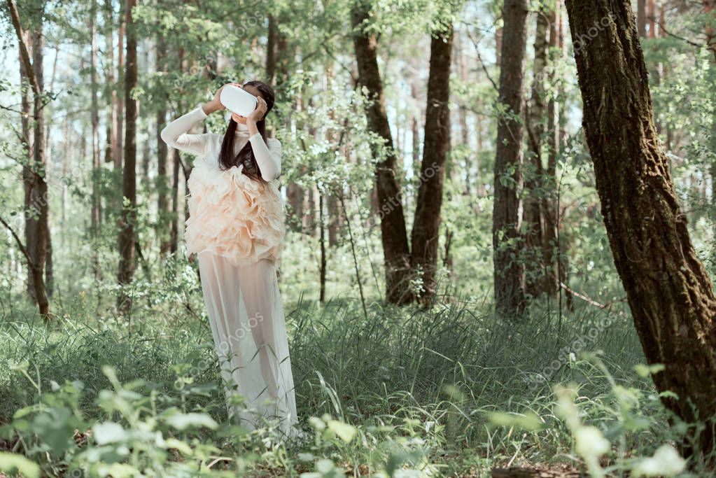 tender woman in white swan costume and vr headset standing on forest background