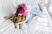 pohled na dívku s barevným účesu, sedícího v posteli se psem