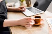 Ausgeschnittene Ansicht einer Frau, die eine Tasse Kaffee hält und am Tisch sitzt
