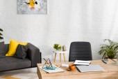 fa asztal jegyzetfüzetekkel, laptop és csésze kávé a nappaliban kanapéval