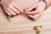 cropped view of man putting medical marijuana in marijuana crusher