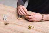 abgeschnittene Ansicht des Mannes, der medizinisches Marihuana in Marihuana Brecher auf den Tisch legt