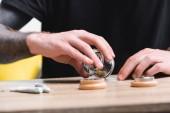 abgeschnittene Ansicht eines Mannes, der medizinisches Cannabis auf Tabakpapier legt, während er mit Joints am Tisch sitzt