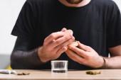 abgeschnittene Ansicht eines Mannes, der Kräutermühlen mit medizinischem Marihuana schließt, während er am Tisch sitzt