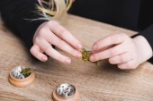 cropped view of girl at table holding medical marijuana