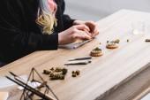 abgeschnittene Ansicht der Frau rollen Joint, während am Tisch mit medizinischem Cannabis, Kräuterschleifer und Gelenken sitzen
