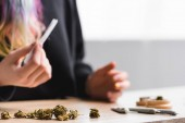 Cropped view of girl holding joint at table with medical marijuana