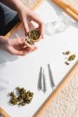 Ansicht von oben: Mädchen schließt Kräutermühle mit medizinischem Cannabis im Sonnenlicht