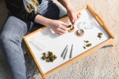 cropped view of girl putting medical cannabis in herb grinder