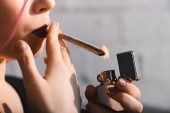 cropped view of girl lighting up and smoking joint with medical marijuana
