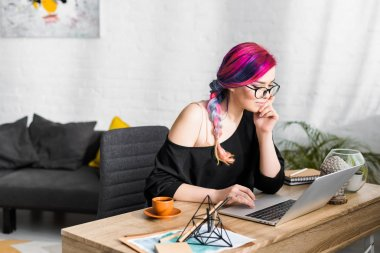 beautiful girl with colorful hair sitting behind table and using laptop in living room