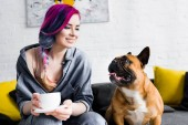 Photo attractive girl with colorful hair holding cup of coffee and sitting on sofa near french bulldog
