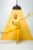 attractive blonde woman in sunglasses holding hanger and posing on white and yellow