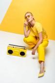 stylish woman sitting near retro boombox on white and yellow