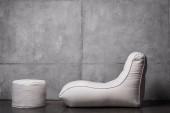 židle z fazolí v blízkosti bílé kulaté stolice na šedé