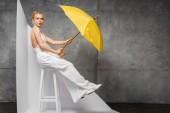 atraktivní blondýnka seděla na židli a držela žlutý deštník na bílém a šedém