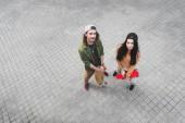 pohled na krásnou ženu a muže na skateboardy s výhledem na kameru