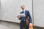 nízký úhel pohledu obchodníka na formální opotřebení stojící poblíž skateboard, s novinami v ruce