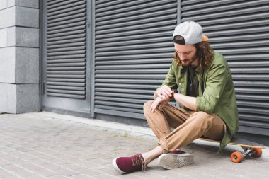 handsome man sitting on skateboard, looking at smartwatch