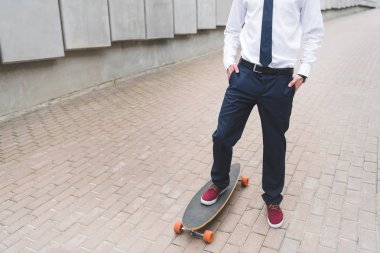 Cropped view of businessman in formal wear standing on skateboard stock vector