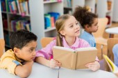 selective focus of cute kid holding book near african american children