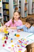 selektivní zaměření veselých dětí, které drží v blízkosti papírů štětce