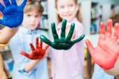 selective focus of kids showing colorful hands with gouache paint