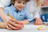 selective focus of woman drawing with happy kid