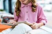 oříznuté zobrazení podřízeného sezení a čtení knihy v knihovně