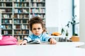 unatkozik afro-amerikai gyerek ül a könyv közelében a könyvtárban
