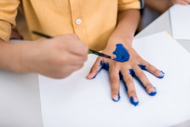 Cropped view of child holding paintbrush while painting on hand stock vector