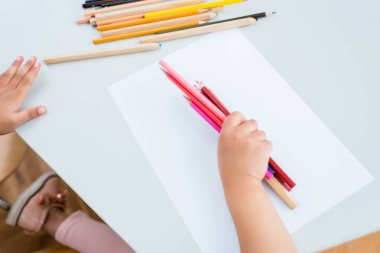 Cropped view of kid holding colorful pencils near paper stock vector