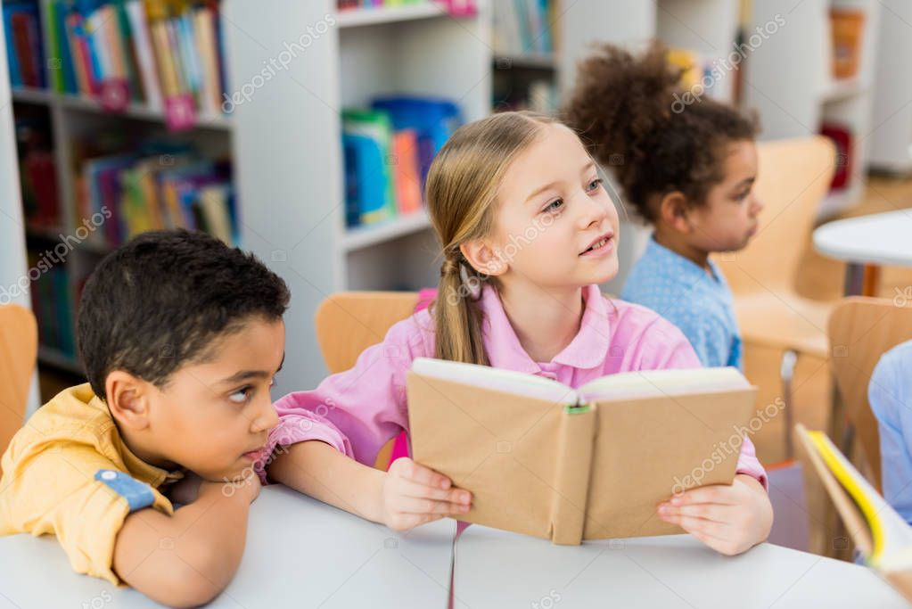 Selective focus of cute kid holding book near african american children stock vector
