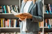 Ausgeschnittene Ansicht einer Frau, die Buch in der Hand hält und in der Bibliothek steht