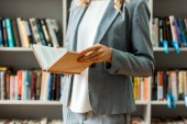 cropped view of woman holding book while standing in library