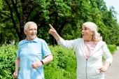 sorpresa donna anziana puntando con il dito durante la corsa vicino al marito nel parco