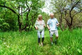 Photo happy woman with grey hair looking at husband while running in park