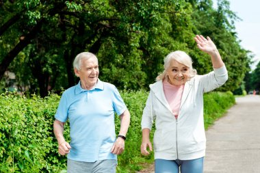 cheerful senior man looking at wife waving hand in park