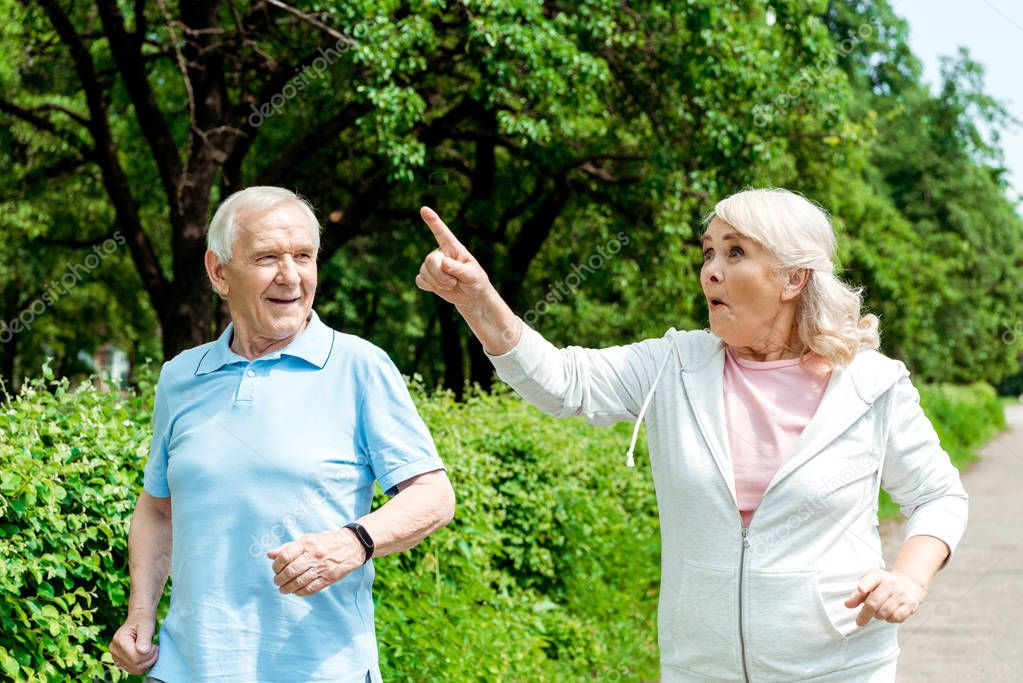 surprised senior woman pointing with finger while running near husband in park