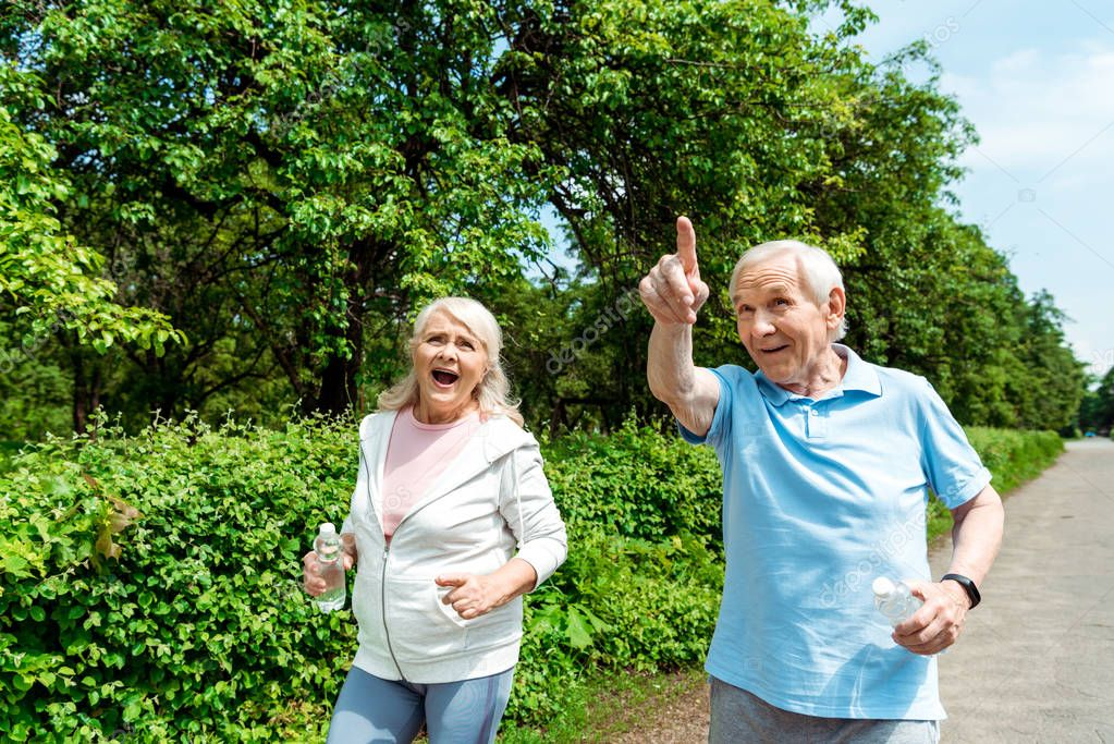 happy senior man pointing with finger near wife holding bottle in park